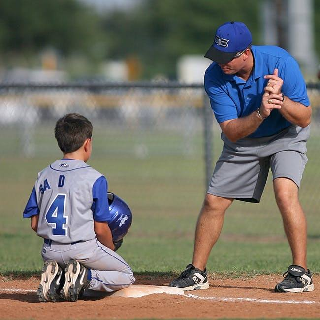 a baseball coach teaching someone